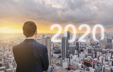 Businessman standing in front of city skyline with 2020 superimposed above