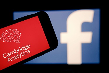 Facebook logo on a screen with a smartphone in front of it showing Cambridge Analytica logo